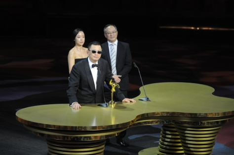 Wong Kar Wai receives the Best Director Award at the 8th Asian Film Awards from Ambassador Jeon Do Yeon and Johnnie To